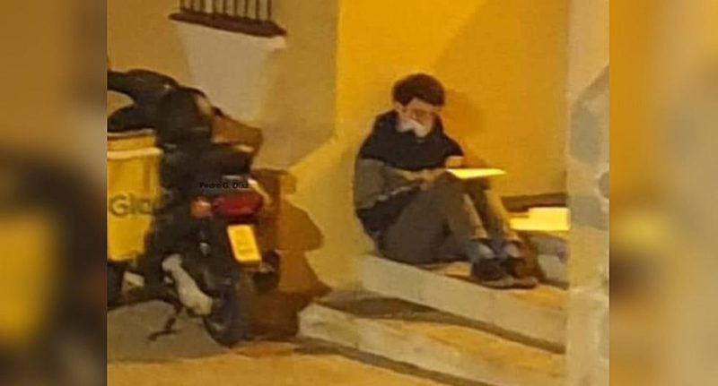 Delivery man is caught studying under a lamppost while waiting for his next delivery