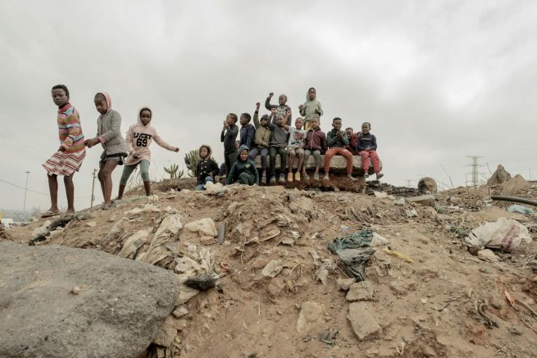 Los niños se reúnen en lo alto de una colina esperando al presidente del Congreso Nacional de Sudáfrica, Cyril Ramaphosa, antes de una visita al asentamiento de Nomzamo en Soweto, el 18 de septiembre de 2021 (AFP/LUCA SOLA)