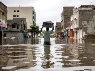 Un hombre lleva una maleta en la cabeza mientras cruza una calle inundada en Dakar, Senegal, el 20 de agosto de 2021 (AFP/JOHN WESSELS)