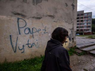 """Una mujer pasa frente a un muro con la inscripción """"Papa, bienvenido"""" en la barriada Lunik IX de Kosice (Eslovaquia), el 30 de agosto de 2021 (AFP/VLADIMIR SIMICEK)"""