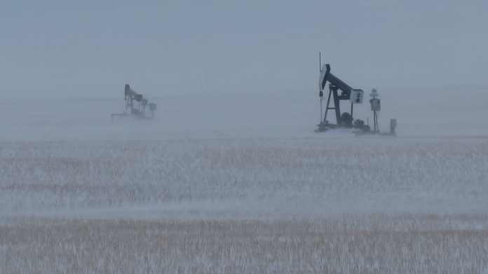 2 natural gas pumps in a field in snow storm