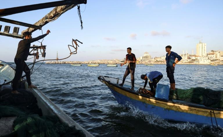 Un pescador palestino lanza una cuerda para formar una caravana con otro barco en la costa de la ciudad de Gaza, el 22 de septiembre de 2021 (AFP/MAHMUD HAMS)