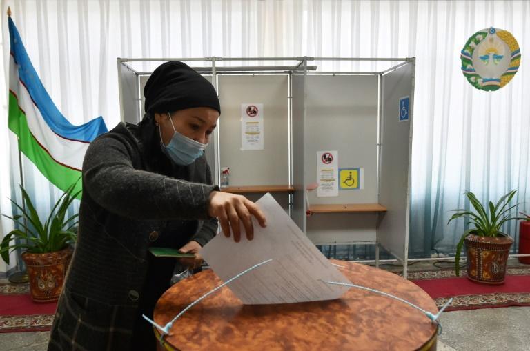 Una mujer deposita su papeleta en la urna en un colegio electoral de Tashkent con motivo de las elecciones presidenciales, el 24 de octubre de 2021 en la capital de Uzbekistán (AFP/Vyacheslav Oseledko)